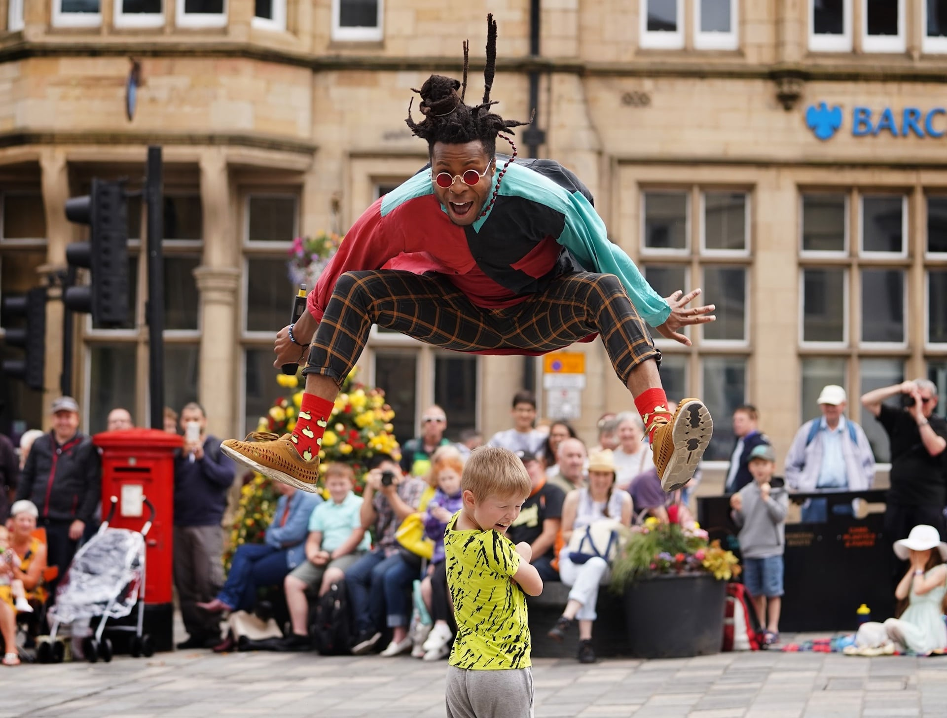 Man leaping over a child at Durham Brass Festival