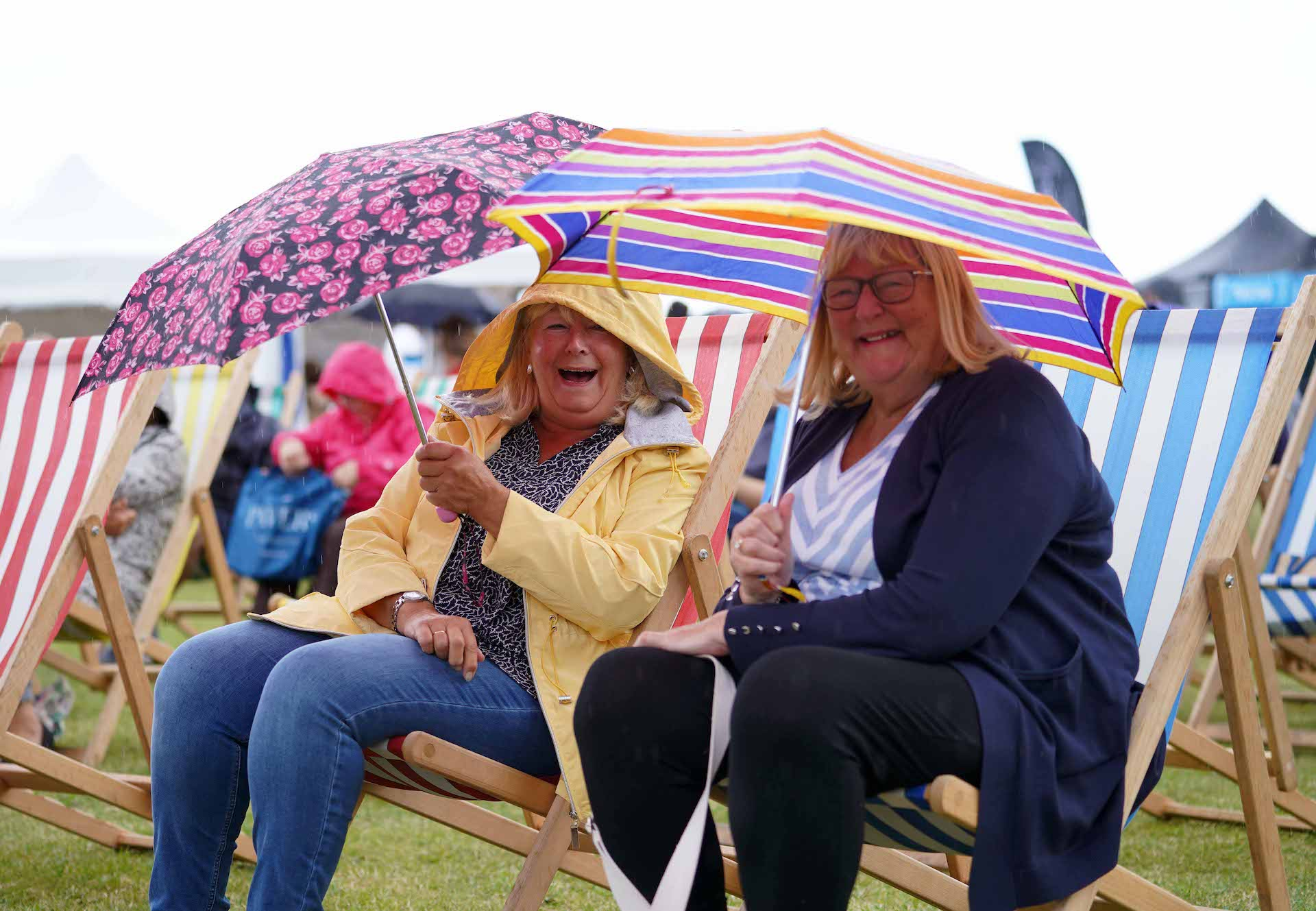 Ladies sitting in beach chairs, holding umbrellas, at Seaham Food Festival