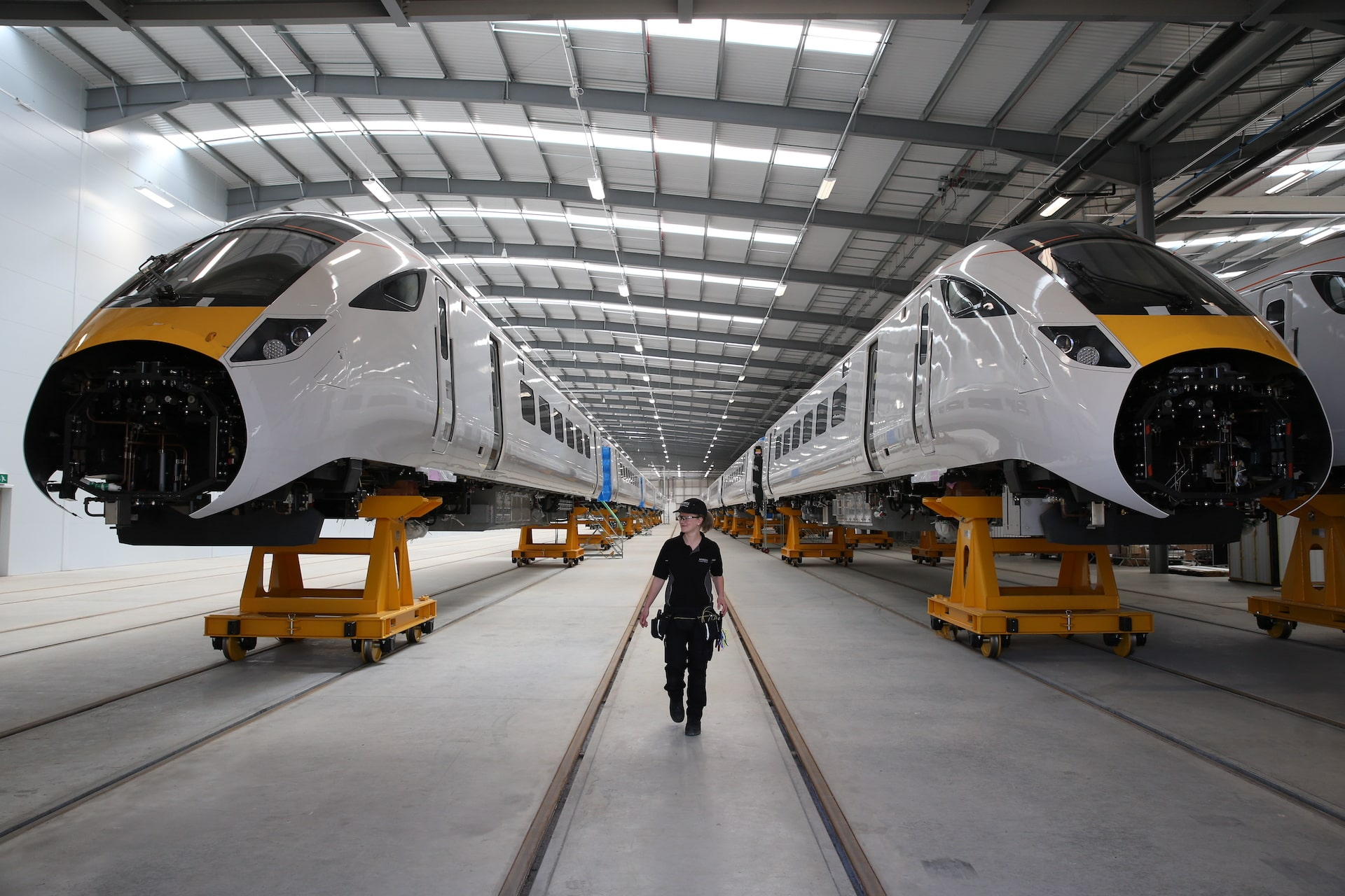 Woman stood between two Hitachi Rail trains in factory