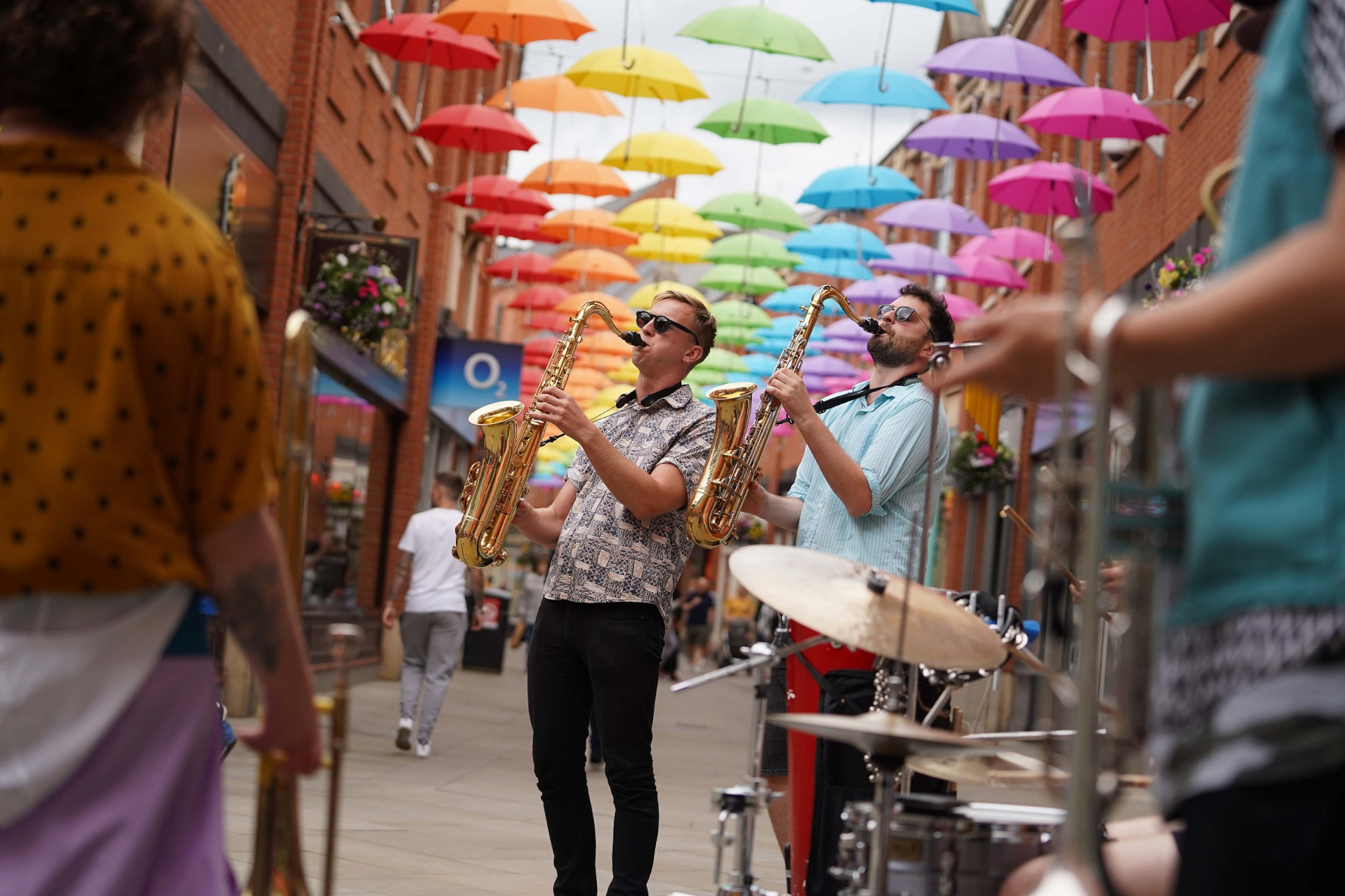 BRASS musicians playing under colourful umbrella