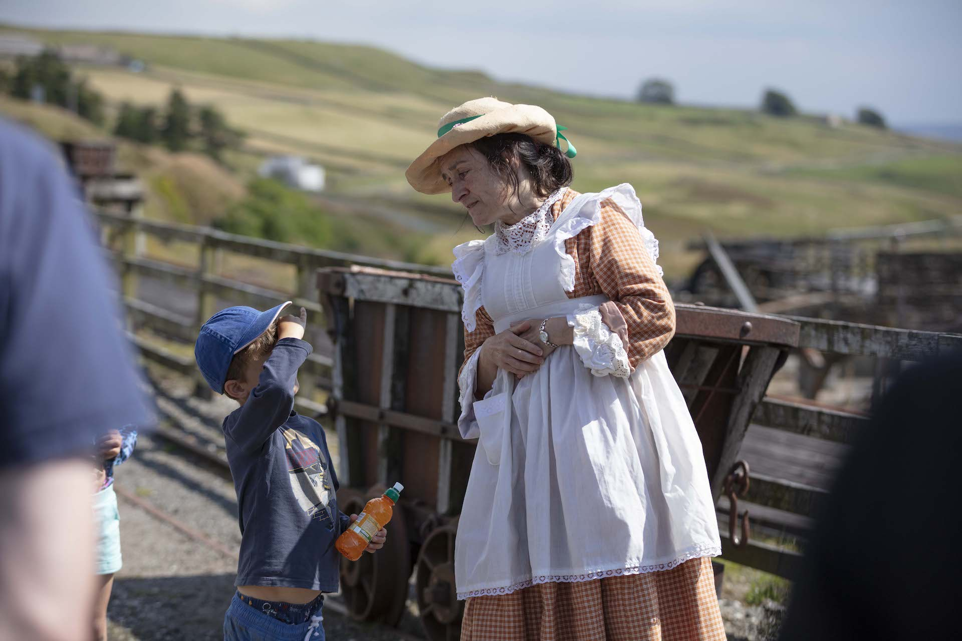 Lady in old traditional clothes talking to young boy at Killhope Mine